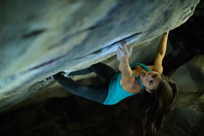 a young woman rock climbing at night