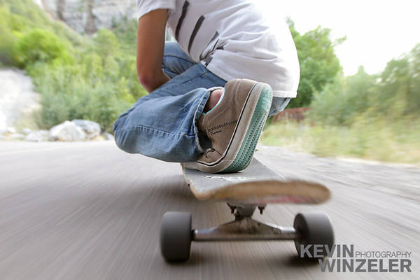 A long boarder is pinned to the pavement during a downhill run.  This image was an outtake during an editorial shoot. Longboard, Park City, Spinning, Trail, Utah, Vertical, action, active, angle, asphalt, axis, blurred, closeup, extreme, fast, footwear, kneeling, lifestyle, longboarder, low, motion, movement, one, outdoors, person, perspective, promenade, rolling, rubber, salt lake, shoe, sidewalk, skateboard, skateboarding, skating, sky, sole, speed, sports, view, wheel,