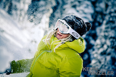 Snowboarder stops for a break during a powder run and gets into a snowball fight with her friends; enjoying the winter wonderland.
