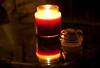 Nice shot of a red candle and container top on a glass table.  The reflections are pretty cool.