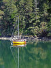 Anchored sailboat in a hidden cove. The smooth water allows for a nice reflection.