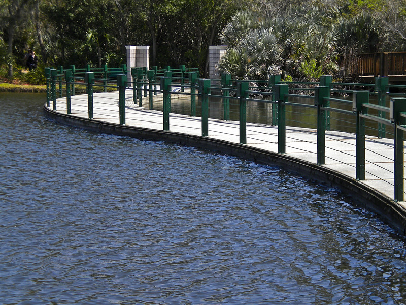 A floating walkway over a man made lagoon.