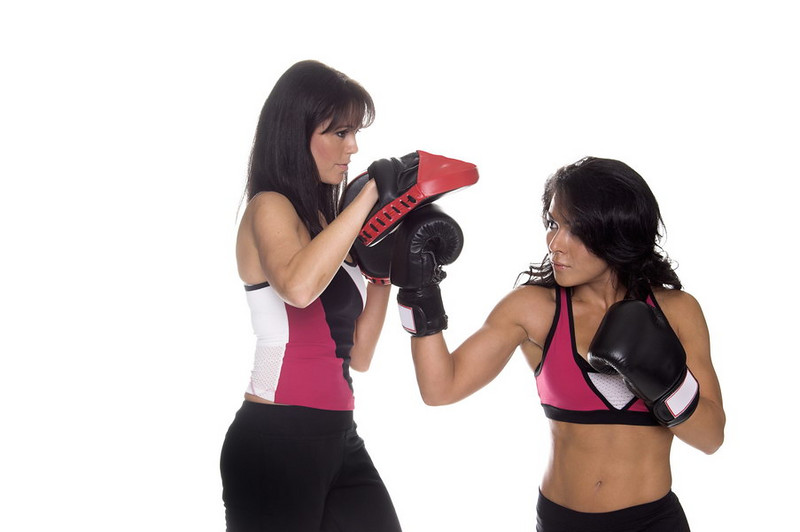 Two beautiful female boxers training on focus mitts with the puncher throwing a right uppercut