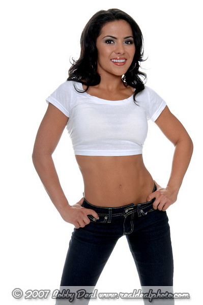 Young female personal fitness trainer in designer jeans and a half t-shirt with her hands on her hips