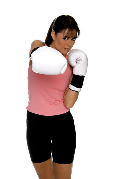 Healthy young woman in white boxing  gloves shoots a strong right cross during a boxing workout.