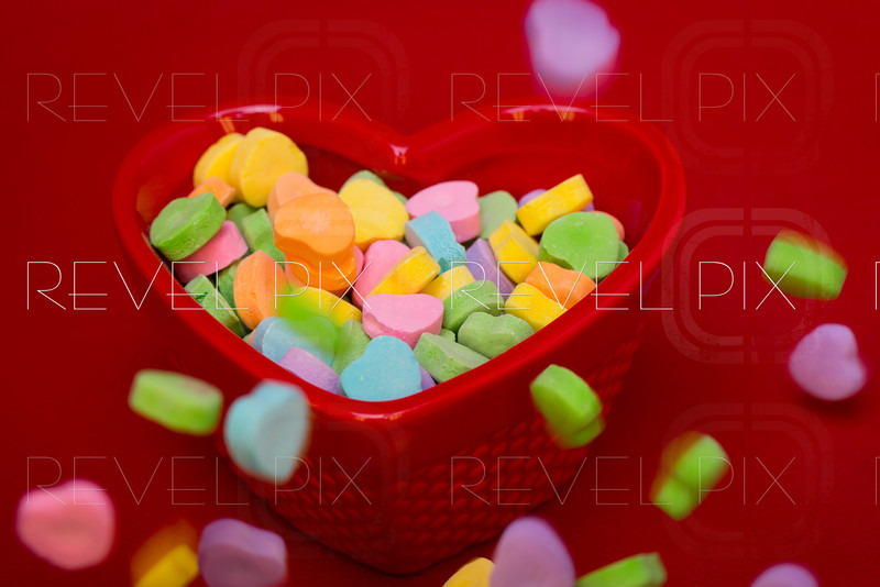 heart candies fall around a heart shaped cand dish on a red textured background.