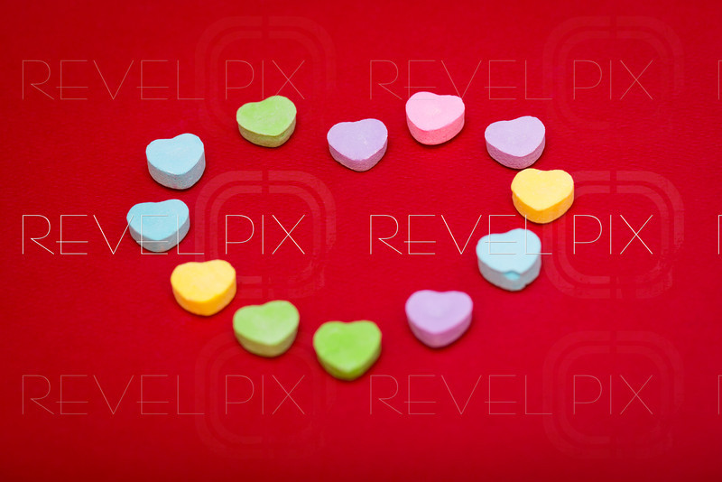 heart candies in the shape of a heart on a red textured background. focus on back candies.
