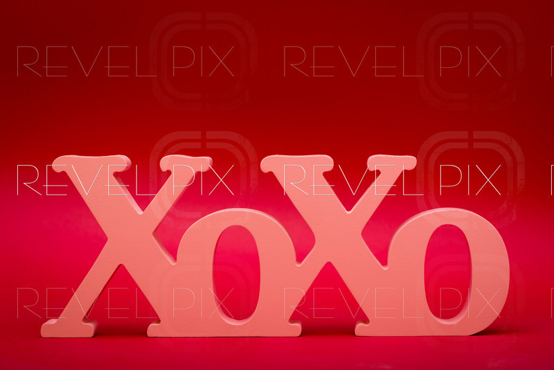 a wood carved X and O's symbol stands up on a red textured gradient background.