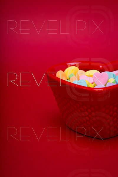 a candy dish is filled with heart candy on a red textured background. pink candy is pointed at camera for your own text. copyspace.