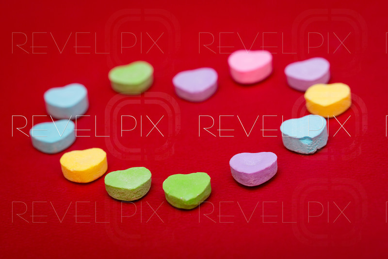heart candies in the shape of a heart on a red textured background. focus on front candies.