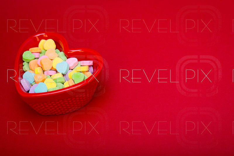 a heart shaped candy dish filled with heart candies left justified on a red textured background. copyspace