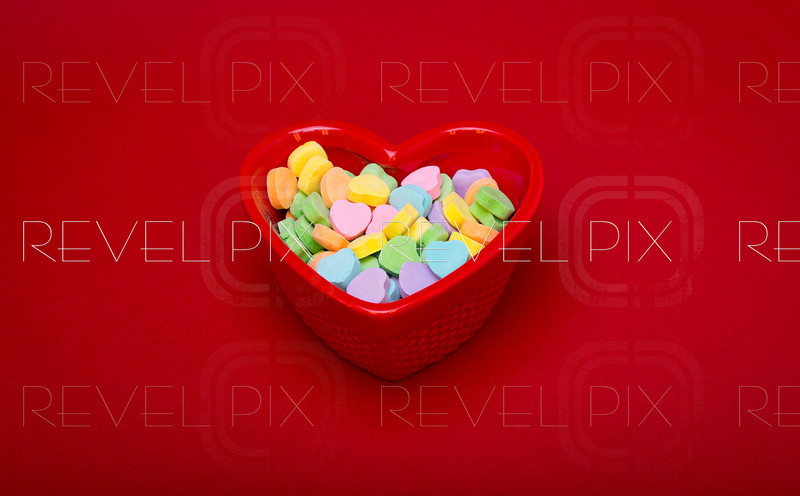 a medium shot of a heart shaped candy dish on a red textured background filled with candy hearts