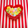 a heart shaped candy dish filled with candies is on a red and white striped background.