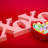a wood carved X and O's symbol lays on a red textured gradient background.a wood carved X and O's symbol stands up on a red textured gradient background with a heart shaped candy dish full of candies in front
