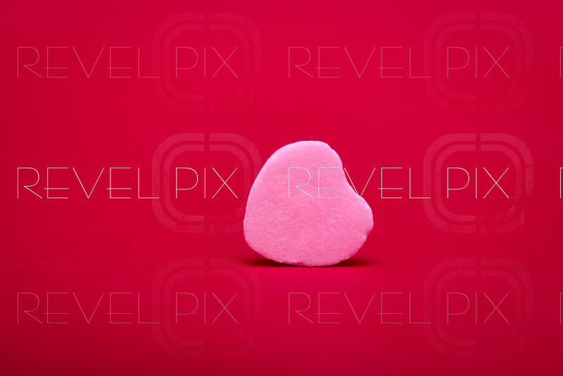 a pink heart shaped candy lies on its side on a red textured background