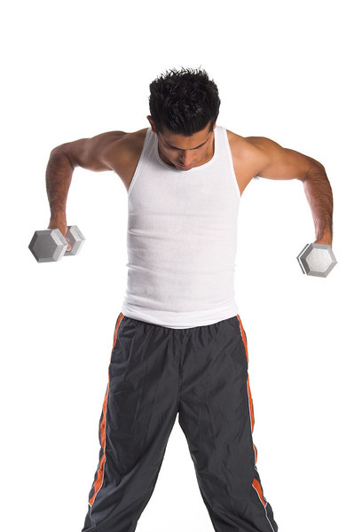 Young Hispanic man working out in the gym with free weights