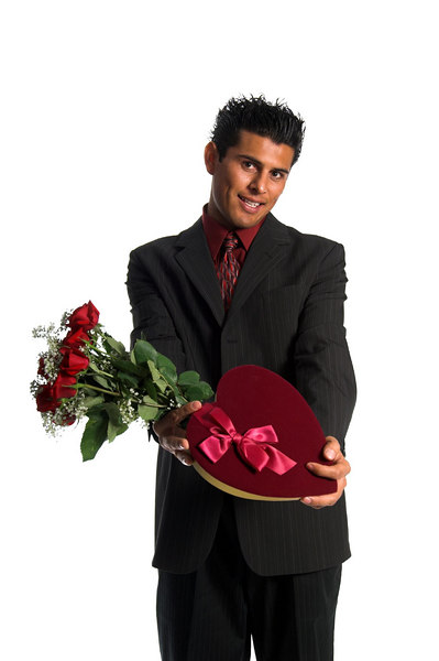 Handsome young Hispanic busniess man in a suit presenting a dozen red roses and a heart shaped box of candy