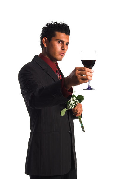 Handsome young Hispanic man holding a glass of wine and a bouquet of flowers proposing a Valentine Day toast