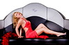 Sexy blond woman in a long red dress and a red and black feather boa laying in a big retro clam shell lounge booth