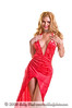 Blond fashion model wearing a low cut  vintage style red dress cut high up the front