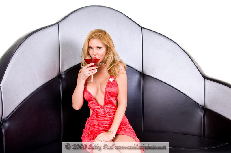 Blond fashion model wearing a low cut  vintage style red dress cut high up the front sitting on a vintage lounge booth