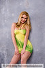 Blond fashion model in a short tight fitting green and yellow party dress against a concrete background