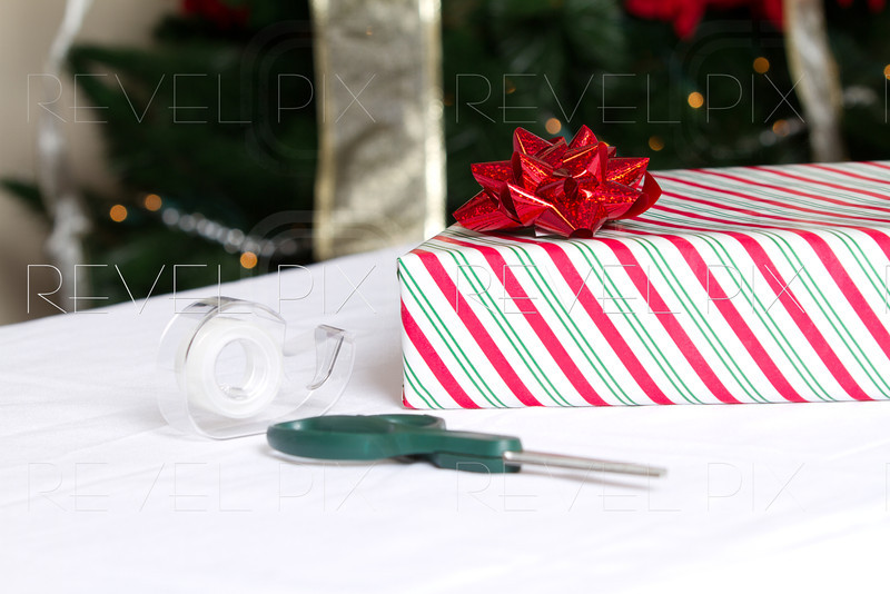 a horizontal shot of a present wrapped in striped wrapping paper with scissors and tape in foreground