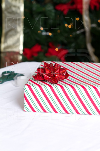 a vertical shot of a present wrapped in striped wrapping paper with scissors and tape in background