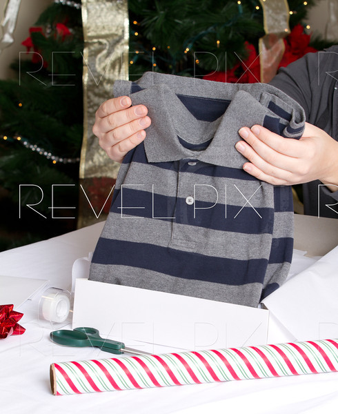 someone places a polo shirt into a box in preparation to wrap it for the holidays