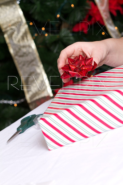 someone is about to place a red ribbon on a striped gift wrapped present. christmas theme.