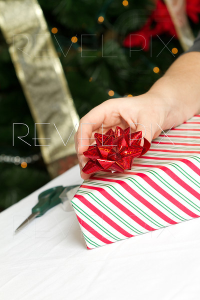 someone places a red bow on a wrapped gift. Christmas tree in background