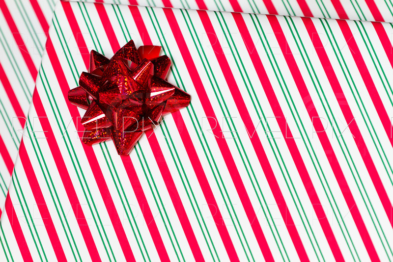 a horizontal close up shot of a gift with striped wrapping paper and a ribbon bow.