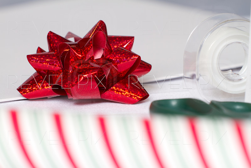 a Christmas Bow close up with striped wrapping paper in the foreground. tape and scissors near by.