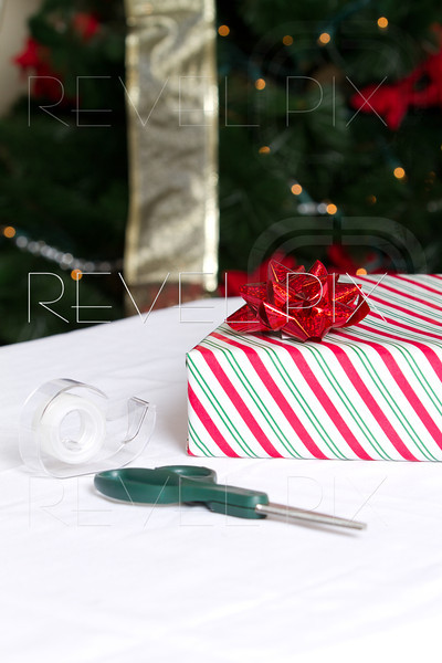 a vertical shot of a present wrapped in striped wrapping paper with scissors and tape in foreground