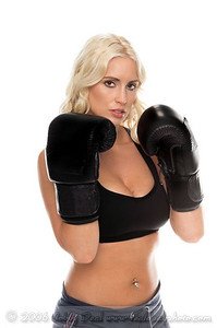 Healthy young woman in black boxing gloves ready in her fight stance