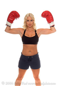 Healthy young woman in red boxing gloves flexing her biceps