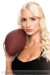 Closeup of a beautiful young blond woman posed with a football on her shoulder