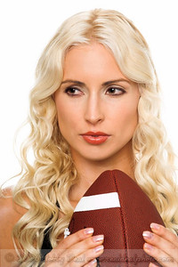 Closeup of a beautiful young blond woman posed with a football