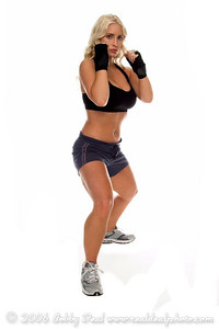 Healthy young woman in hand wraps stands ready in her fight stance during a cardio boxing workout.  Full Body