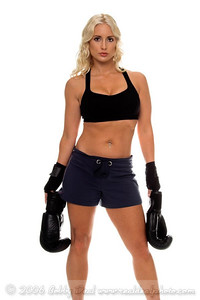 Healthy young woman in hand wraps stands holding her boxing gloves at her side as she prepares for a cardio boxing workout.