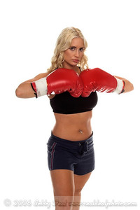 Healthy young woman in red boxingbrings her fist together in a challenge as if to ask, you want some of this?
