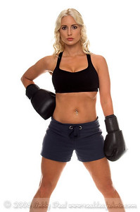 Healthy young woman in black boxing  gloves stands confidiently with one hand on her hip.