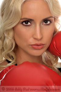 Beautiful young woman in red boxing in her fight stance glares at her compitition in challenge