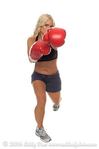 Healthy young woman in red boxing  gloves shoots a left jab during a cardio boxing workout.  Cardio Boxing and Cardio Kick boxing are high energy fat burning, muscle building workouts and are two of the fastest growing fitness workouts in the United States.