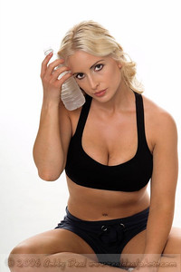Beautiful blond woman in shorts and a sports bra sits crosslegged on the floor with a cold water bottle against her head after a hard areobic workout