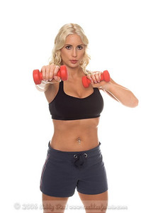 Beautiful young blond woman in shorts and a sports bra working out in the gym with small hand weights