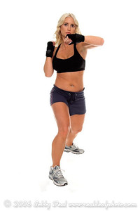 Healthy young woman in hand wrapsthrows a strong left elbow during a cardio boxing workout.