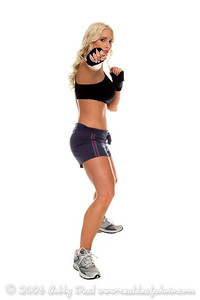 Healthy young woman in hand wraps shoots a straight right hand during a cardio boxing workout.  Full body
