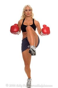Healthy young woman throws a high knee kick during a cardio kickboxing workout