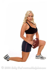 Beautiful young blond woman in shorts and a sports bra kneeling with a football